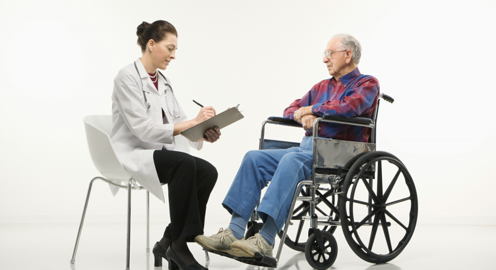 Doctor taking notes of discussion with older man in a wheelchair