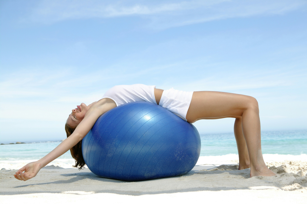 Girl Stretching her back over a beach ball