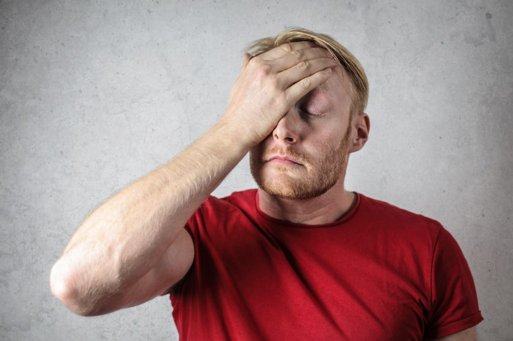 Man in a red t-shirt holding his head worried and stressed. Stress Impact